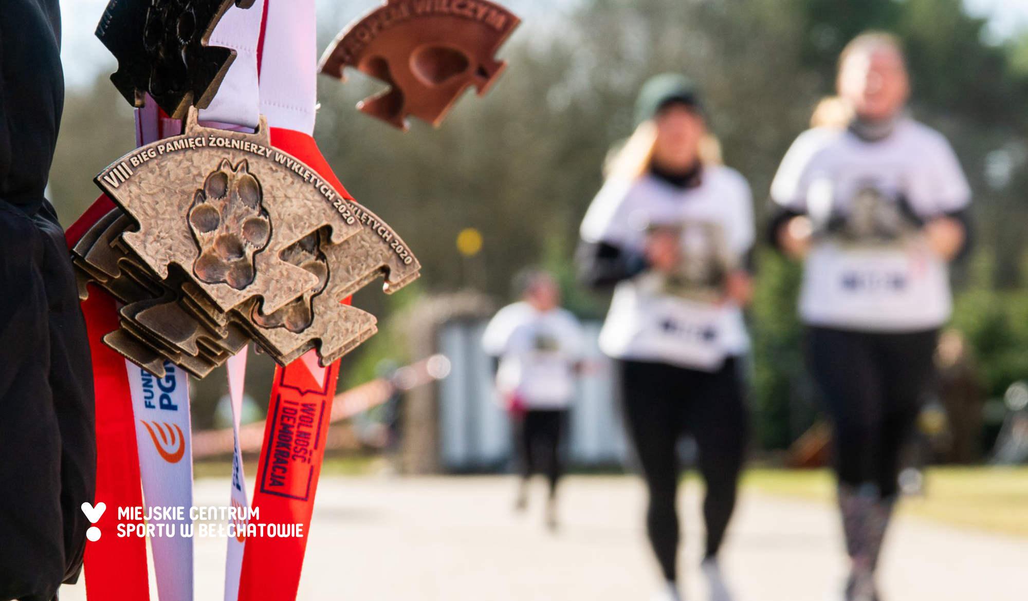 Medale biegu Tropem Wilczym 2020 oraz finiszujący zawodnicy w tle