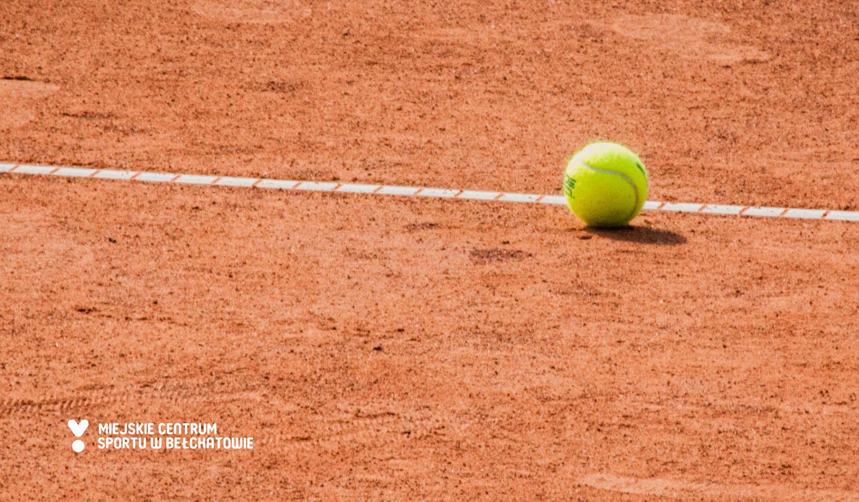 grafika przedstawia piłkę do tenisa ziemnego leżąca na korcie tenisowym