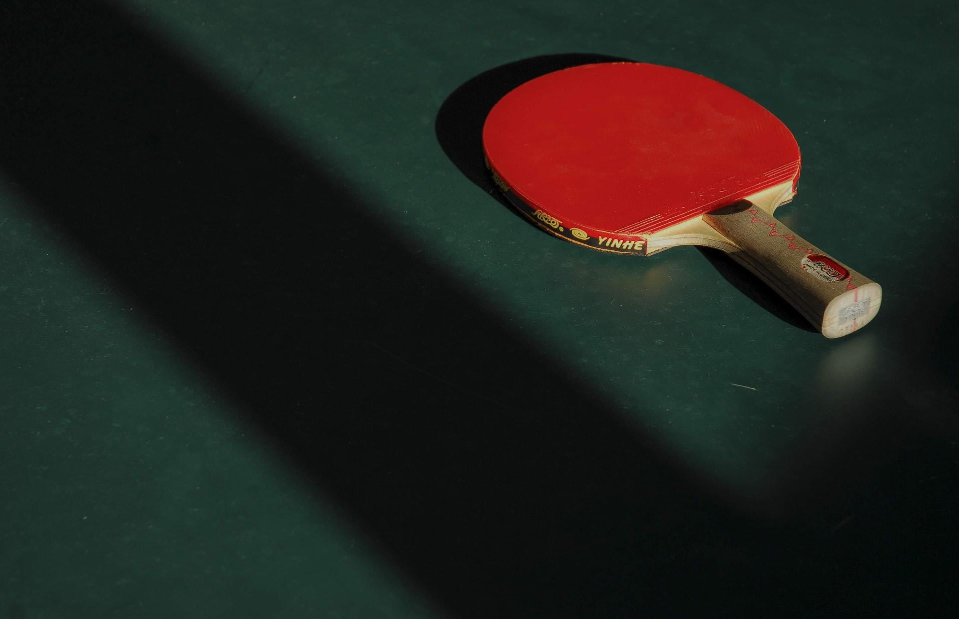 zdjęcie przedstawia rakietkę do tenisa stołowego leżącą na stole tenisowym