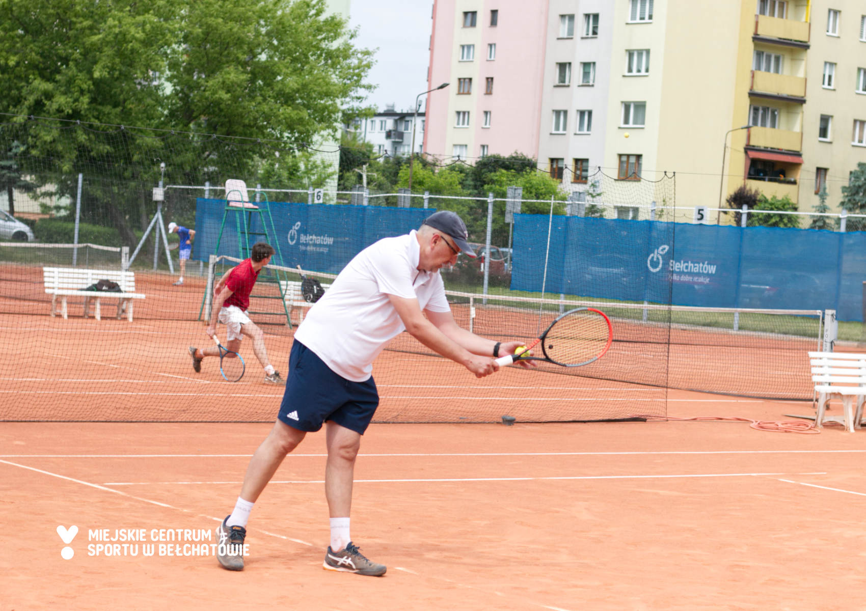 zdjęcie przedstawia mężczyznę w stroju sportowym, który w ręku trzyma rakietę i piłkę do tenisa ziemnego