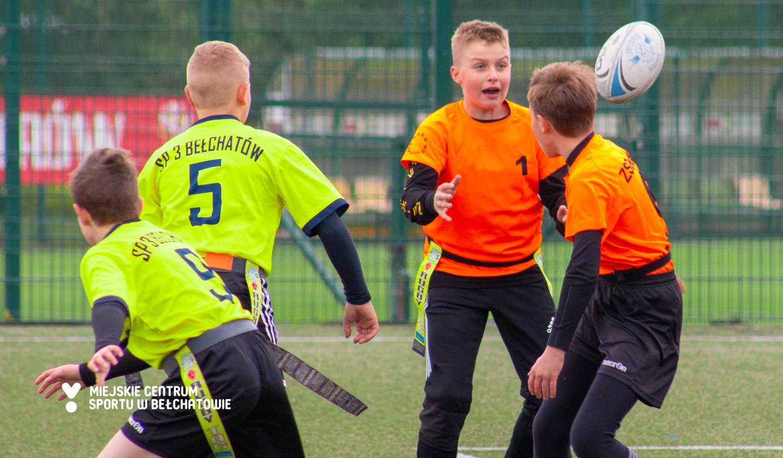 Na zdjęciu widoczni są uczniowie grający w rugby tag na boisku, którzy podają do siebie piłkę do rugby