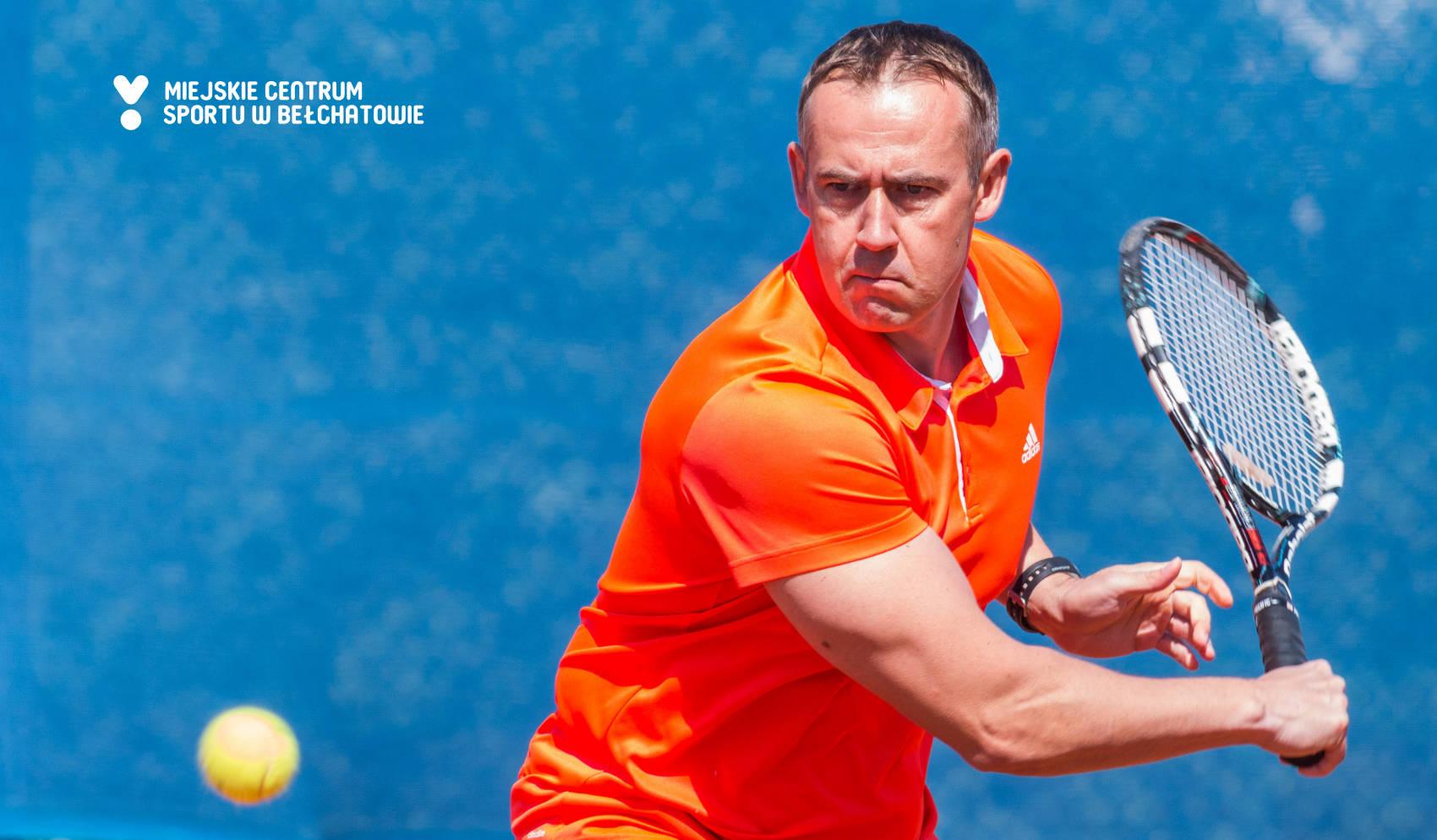 na zdjęciu widoczny jest mężczyzna trzymający rakietę do tenisa ziemnego, który odbija piłkę do tenisa ziemnego